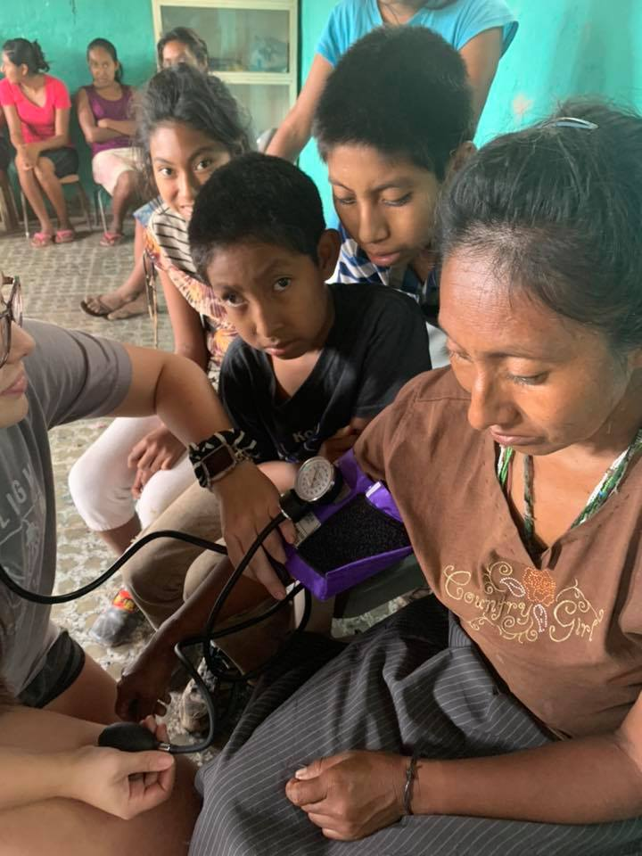 nurse checking a woman's blood pressure while her children look on in a makeshift clinic in honduras